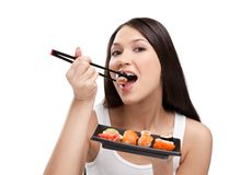 Attractive woman eating sushi Stock Images