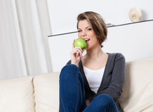 Attractive woman eats a green apple Stock Photography