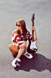 Attractive woman with electric guitar outdoor fashion portrait Stock Photo