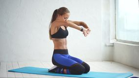 An attractive woman is engaged in stretching in the gym, she is sitting on a rug. A pretty and athletic woman is engaged in stretching the upper back in the gym stock video