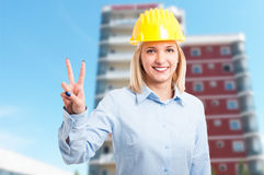 Attractive woman engineer wearing helmet showing peace. Attractive woman engineer wearing yellow protection helmet showing peace gesture and smiling Royalty Free Stock Images