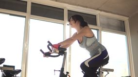 Attractive woman enhancing her endurance while working out on an exercycle. portrait of a beautiful girl in the gym on a. Enhancing her endurance while working stock video