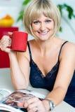 Attractive woman enjoying coffee and reading magazine Stock Photos