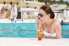Attractive woman enjoying a poolside cocktail Royalty Free Stock Photo