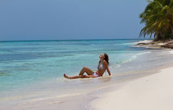 Attractive woman enjoying the sun on a beautiful tropical Stock Image