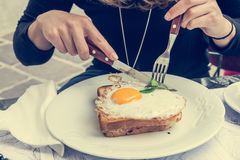 Attractive woman enjoying sunny side up egg on french toast. Stock Images