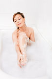Attractive woman enjoys  in the bathtub. Royalty Free Stock Photos