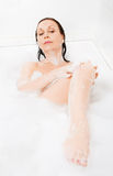 Attractive woman enjoys  in the bathtub. Royalty Free Stock Photography