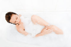 Attractive woman enjoys  in the bathtub. Royalty Free Stock Photo