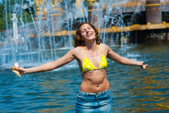 Attractive woman enjoys the cool fountain. Holding ice cream stock photography
