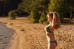 Attractive woman enjoys the sunshine on the beach. Outdoors Royalty Free Stock Images