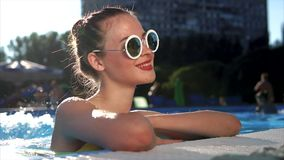 An attractive woman enjoys water treatments in the pool in the summer time stock footage