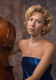 Attractive woman in evening dress with old cello Stock Images
