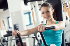 Attractive woman exercising at gym. Biceps workout on a machine Royalty Free Stock Images