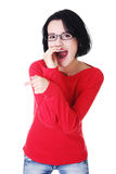 Attractive woman in eyeglasses gossips , points and laughs. Royalty Free Stock Photography