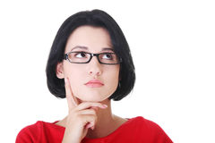 Attractive woman in eyeglasses is looking up and thinking. Stock Image