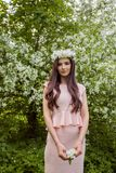 Attractive woman fashion model in flowers wreath in spring park outdoors. Beautiful girl outdoor portrait. Attractive woman fashion model in flowers wreath in stock images