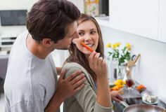 Attractive woman feeding her husband bell pepper Royalty Free Stock Photos