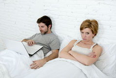 attractive woman feeling upset unsatisfied and frustrated in bed with his husband while the man work on computer laptop ignoring h Royalty Free Stock Images