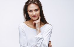 Attractive woman with finger on cheek. Portrait of attractive woman with finger on cheek staring at camera. Beautiful caucasian female model against white stock images
