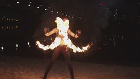 Firegirl performing art of spinning fans at dusk. Attractive woman fireshow artist spinning burning fans mesmerizing with beauty of fiery figures and energy of stock footage
