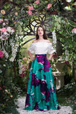 Attractive woman in in floral garden. Blue skirt. Fairy tale Royalty Free Stock Images