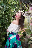 Attractive woman in in floral garden. Blue skirt. Fairy tale Royalty Free Stock Photos