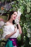 Attractive woman in in floral garden. Blue skirt. Fairy tale Royalty Free Stock Image