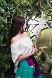 Attractive woman in in floral garden. Blue skirt. Fairy tale Royalty Free Stock Photography