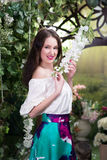 Attractive woman in in floral garden. Blue skirt. Fairy tale Stock Photos