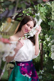 Attractive woman in in floral garden. Blue skirt. Fairy tale Stock Photo