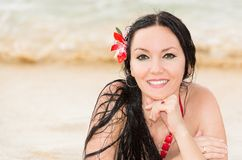 Attractive woman with flower in long hair in bikini on tropical beach sunbathing. Sea background Stock Photos