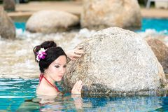 Attractive woman with flower in long hair on tropical beach sunbathing. Sea background Royalty Free Stock Photo