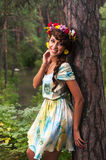 Attractive woman with flower wreath near pine Stock Photos