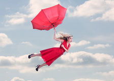 Attractive woman flying in the blue sky Stock Photos