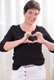 Attractive woman forming hearts with her hands Stock Images