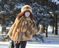 The attractive woman in a fox fur coat is photographed in winter Stock Images