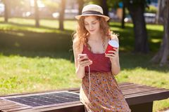 Attractive woman with foxy hair charges mobile phone on bench with solar panel, drinking coffee and checking email or types