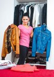 Attractive woman in front of closet full of clothes Royalty Free Stock Photo