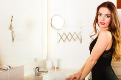 Attractive woman in front of mirror in bathroom. Royalty Free Stock Photography