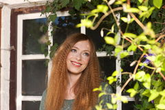 Attractive woman in front of an old window. In the garden Stock Images