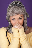 Attractive woman in furry winter hat. Blowing into her hands to keep warm against the winter chill Stock Photography