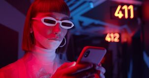 Attractive woman in futuristic shades typing message while communicating in social media. Female clubber with make up