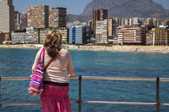 Attractive woman gazes over Playa de Levante, Benidorm. Royalty Free Stock Photos