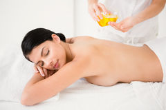 Attractive woman getting massage oil on her back Stock Photos