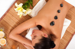 Attractive woman getting spa treatment. Isolated on white background. Hot Stones Massage Royalty Free Stock Photography