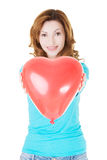 Attractive woman giving a baloon heart. Stock Photos