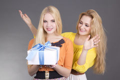 Attractive woman giving a present to her surprised friend Stock Images