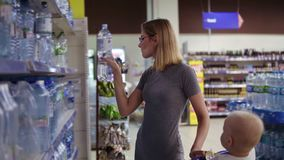 Attractive woman in glasses is choosing a bottle of water in beverages department in the supermarket, while her little stock video footage