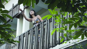 Attractive woman going out on the balcony and looking at the sky if it is rainning stock video
